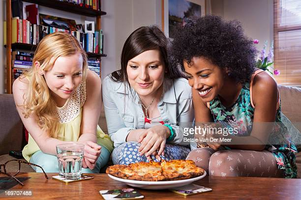 women looking at large pizza ready to be eaten. - only young women stock pictures, royalty-free photos & images