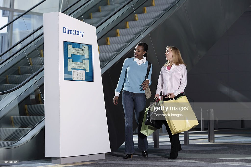 Women looking at mall directory : Stockfoto