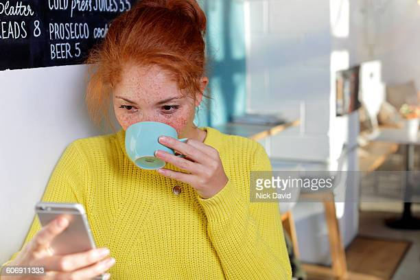 women looking at mobile phone in cafe