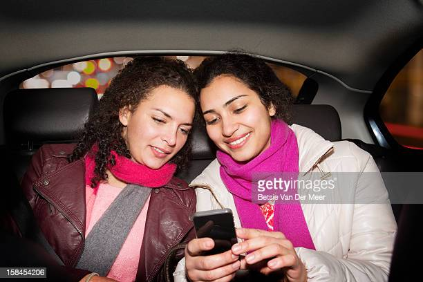 Women looking at phone in back of taxi.