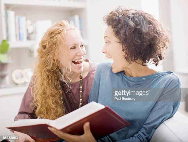 women looking at photo albums - photo album stock photos and pictures