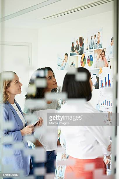 women looking at photos on the wall - brainstorming stock pictures, royalty-free photos & images