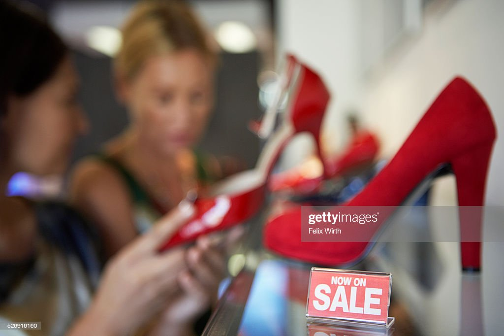Women looking at red high heel shoes on sale : Stock-Foto