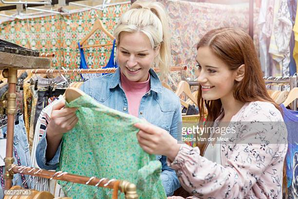 Women looking at shirt in market stall.