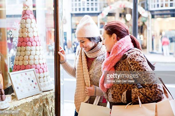 women looking at sweets in shopwindow. - sweet shop stock pictures, royalty-free photos & images