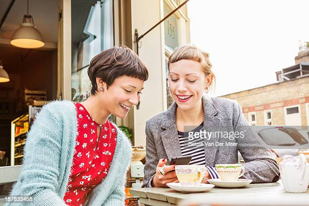 Women looking at the mobile phone while having tea