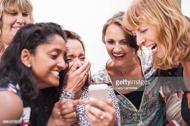 women looking at the smartphone photos they took - lachen stockfoto's en -beelden