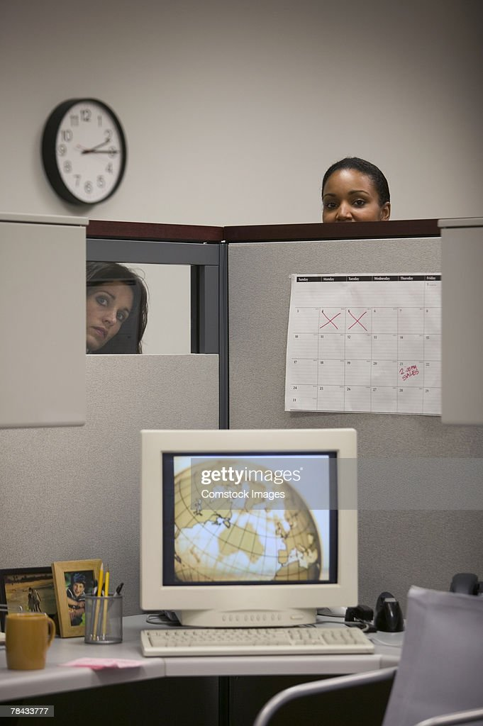 Women looking into cubicle : Stockfoto