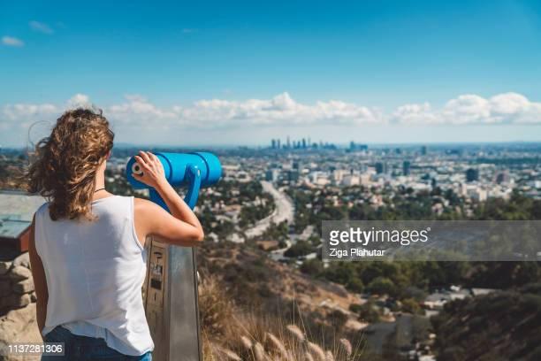 Women looking on downtown LA trough the telescope