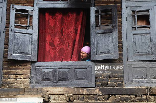 Women looking out from a window as protesters and Indian forces fight pitched battle in a Srinagar locality in the Indian Administered Kashmir The...