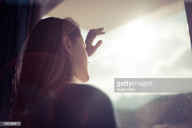 women looking out window - mirar fotografías e imágenes de stock