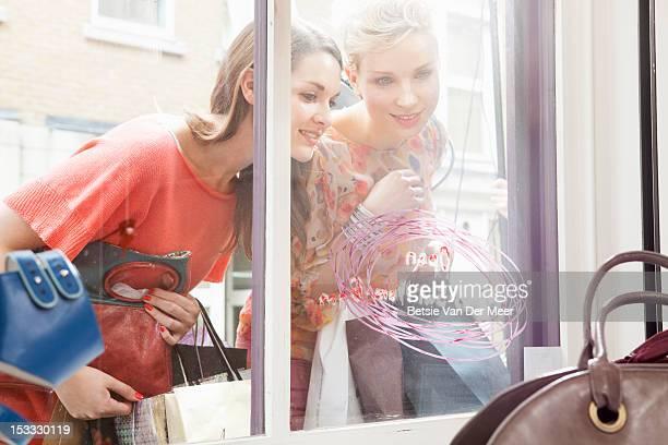 women looking through shop window at bags.
