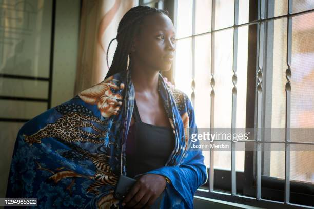 women looking through window contemplating and thinking at home - east africa stock pictures, royalty-free photos & images