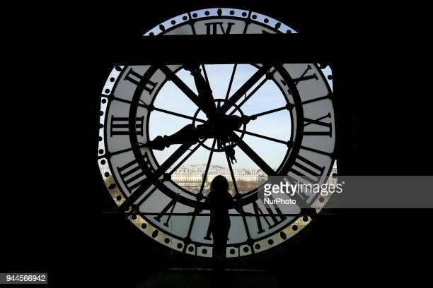 Women looks across the Seine River at a view of Paris through the clock face at the Orsay Museum - the former Gare d'Orsay train station, in Paris,...