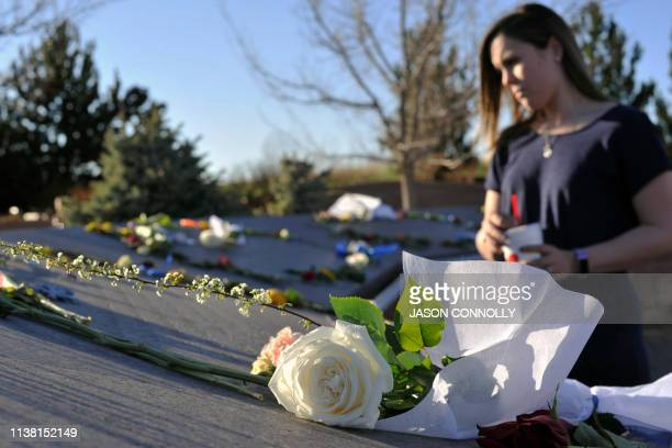 A women looks at the dedications written on the Columbine Memorial at Clement Park in Littleton Colorado before a community vigil for the 20th...