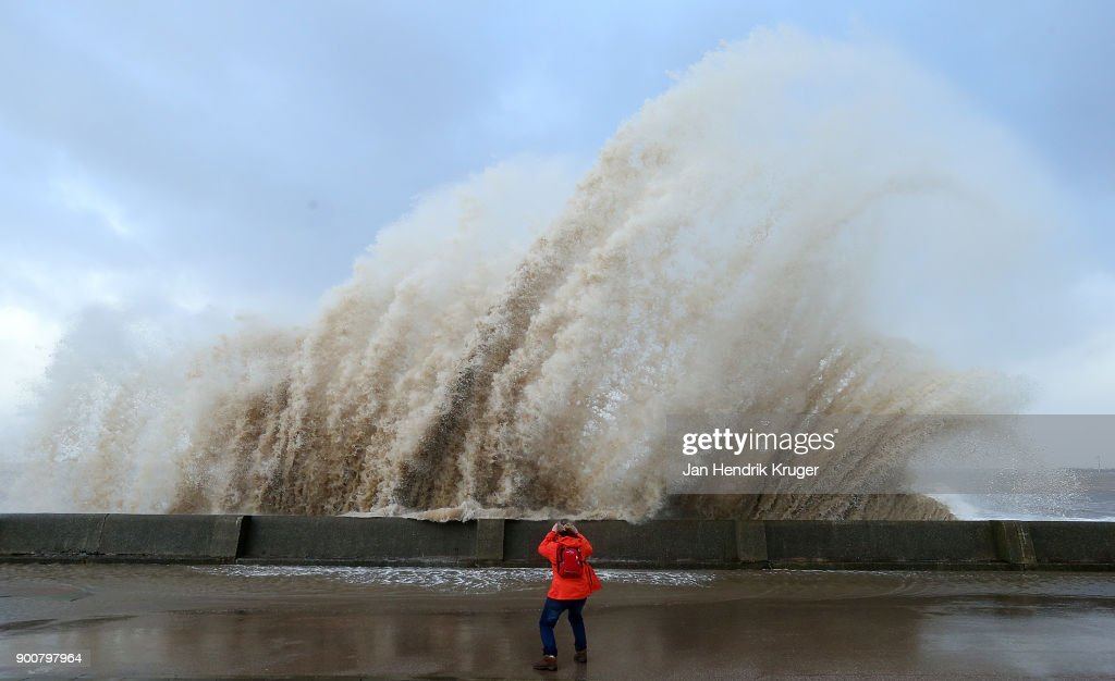 A women looks on as a wave crashes over the tidal wall of the New Brighton Promenade on January 03, 2018 in New Brighton, United Kingdom. A yellow warning is in place as Storm Eleanor brings winds of up to 100mph to parts of the UK and Ireland.