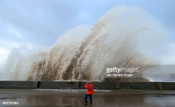 A women looks on as a wave crashes over the tidal wall of the New Brighton Promenade on January 03 2018 in New Brighton United Kingdom A yellow...