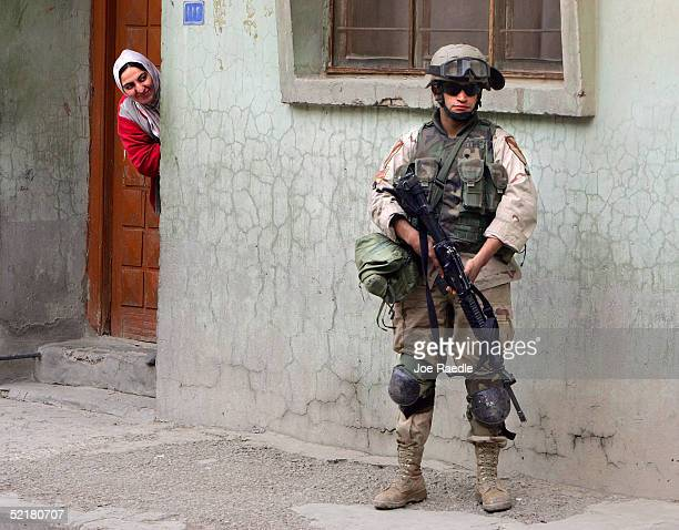 A women looks out her door at a US Army soldier with the 1st Cavalry Task Force 19 on patrol February 11 2005 in the Haifa Street neighborhood of...