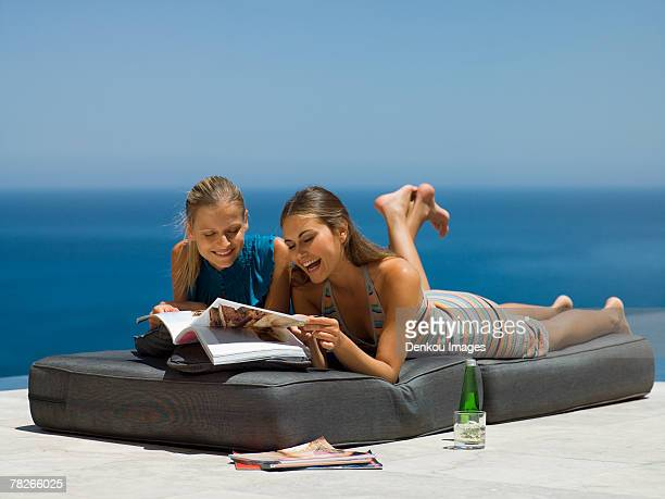 women lying down and reading magazines. - down blouse stockfoto's en -beelden