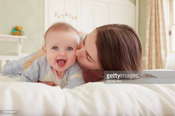 Women lying on bed kissing baby daughter on cheek