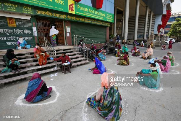Women maintain social distancing outside a bank as they wait to collect their pension during a government-imposed nationwide lockdown as a preventive...