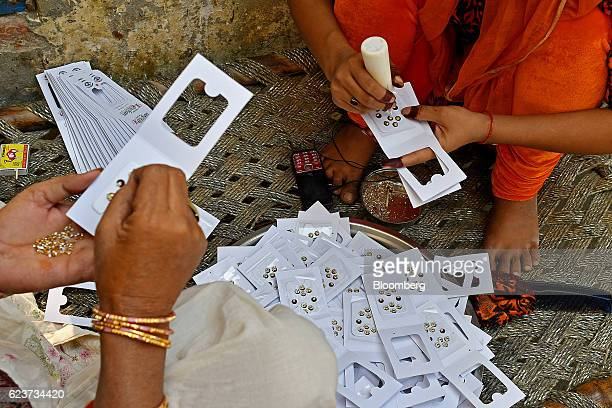 Women make bindis dots commonly worn on the center of the forehead by Hindu and Jain women in a village near Modinagar Uttar Pradesh India on...