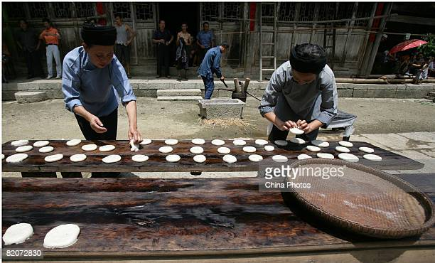 Women make Ciba a traditional cake during the 80th birthday feast of senior citizen Tian Dacui at Keda Village on July 26 2008 in Youyang County of...