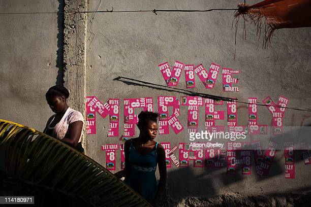 Women make decorations in front of a sign made of posters for newly elected Haitian President Michel Martelly on his inauguration day on May 14 2011...