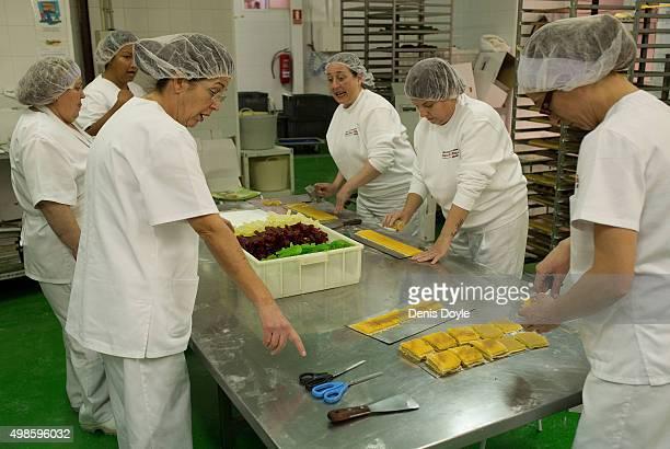 Women make 'Pan de Cadiz' a variety of turron mixed with dried fruits at the Turrones Primitivo Rovira factory on November 24 2015 in Jijona Spain...