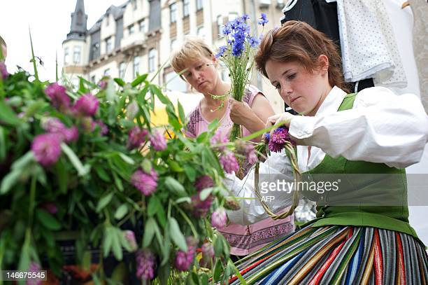Women make wreaths on June 22 2012 at a traditional Grass market in Riga The market is held every year in Latvian cities to prepare for Jani festival...