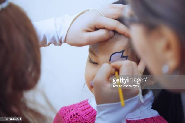 women making face painting for 4-5 years girl - 25 29 years stock pictures, royalty-free photos & images