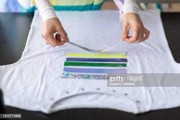 a women making original design t-shirts at home and in online courses. - aplique arte de la costura fotografías e imágenes de stock