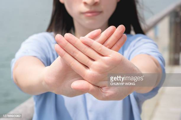 women making stop gesture with two crossed palms - refusing stock pictures, royalty-free photos & images
