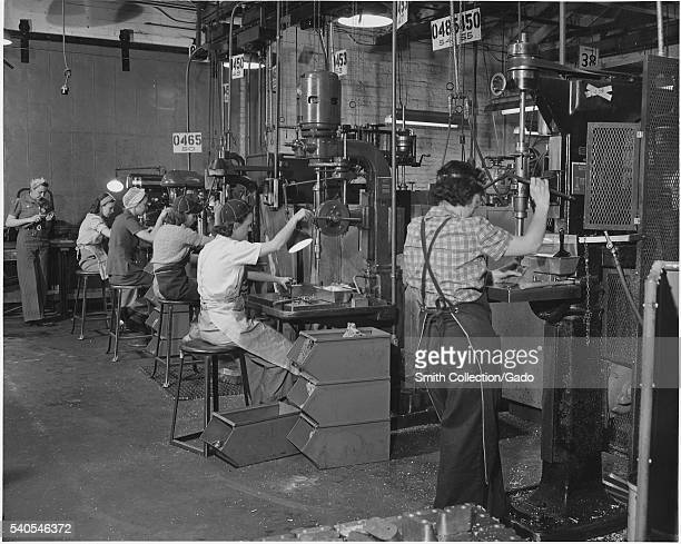 Women man America's machines in a west coast airplane factory where the swing shift of drill press operators is composed almost entirely of women...