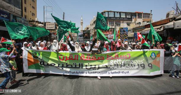 """Women march with flags of the Muslim Brotherhood behind a large banner reading in Arabic """"down with the deal of the century and the normalisation..."""