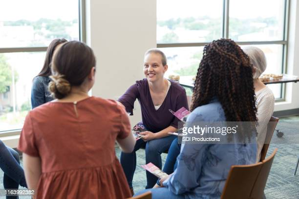 women meet and shake hands at cancer recovery meeting - publication stock pictures, royalty-free photos & images