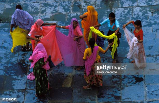 Women meeting for conversation while drying their colourful veils and saris after washing them on a ghat on July 27 1985 near the Pichola Lake in...