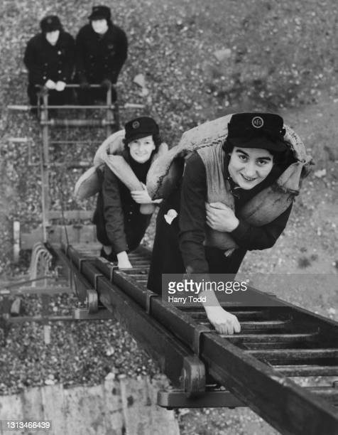 Women members for the Auxiliary Fire Service of the Hastings Fire Brigade undergo training climbing a portable adjustable height extending ladder...
