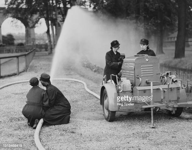 Women members for the Auxiliary Fire Service of the Wolverhampton Fire Brigade undergo training with a portable 80lb water pressure hose and pump...