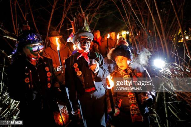 Women members of the Hook Eagle Morris Men make their way to the orchard with villagers during the annual Wassail night in Hartley Wintney 40 miles...