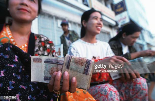 Women money-changers sit by the roadside in Muse with bundles of Burmese Kyat and Chinese Yuan. Muse is the main border crossing between China and...