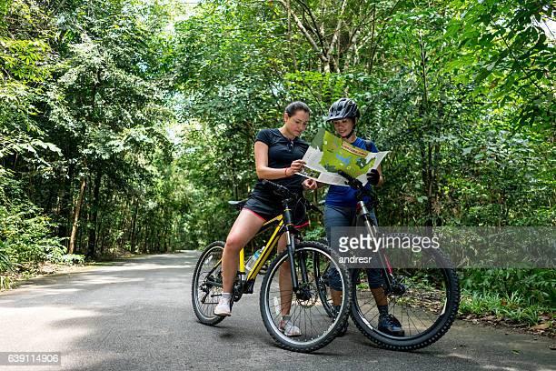 Women mountain biking holding a map