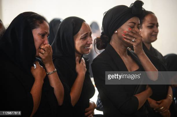 TOPSHOT Women mourn during a memorial ceremony for the seven crew members who died in the Ethiopian Airlines accident at the Ethiopian Pilot...