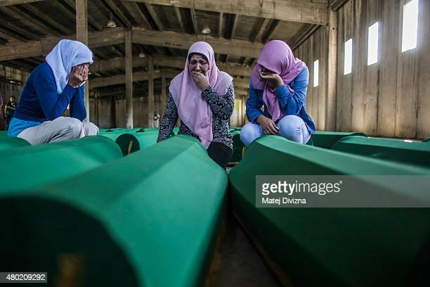 Women mourn over a coffin among 136 coffins of victims of the 1995 Srebrenica massacre in the hall at the Potocari cemetery and memorial near...