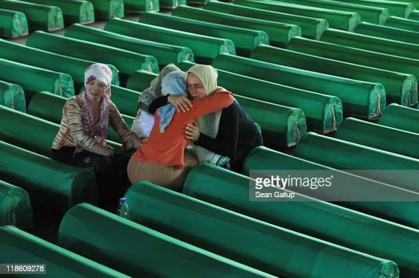 Women mourn over a coffin among 613 coffins of victims of the 1995 Srebrenica massacre in a hall at the Potocari cemetery and memorial near...