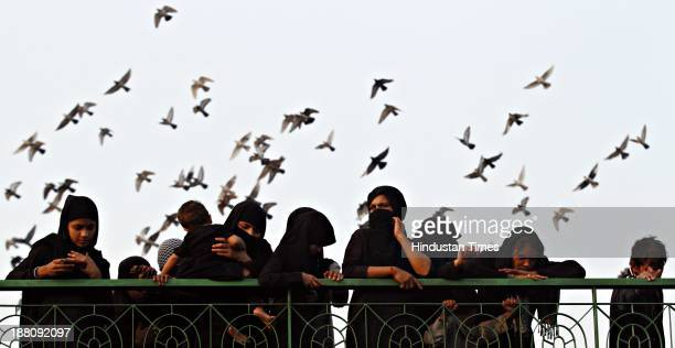 Women mourn to commemorate the martyrdom Imam Hussein during a Muharram procession at a Kashmiri Gate Masjid on November 15 2013 in New Delhi India...