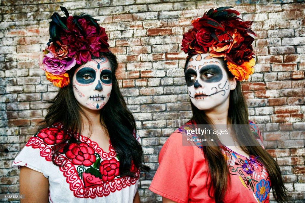 Women near brick wall wearing skull face paint : Stock Photo