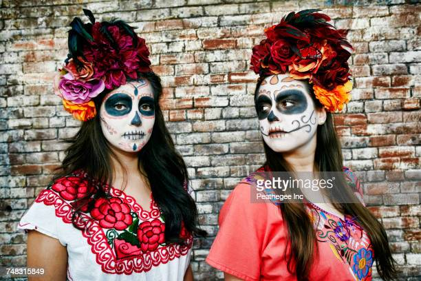 women near brick wall wearing skull face paint - day of the dead stock photos and pictures
