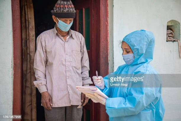 women nurse workers in ppe kit doing door to door surveys in indian village regarding covid-19. - india stock pictures, royalty-free photos & images