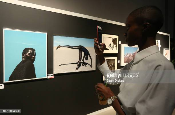 Women NY model Madisin Rian photographs artwork by Dana Scruggs titled 'Adonis' Side Eye' at No Commission Art Fair hosted by Swizz Beatz and...